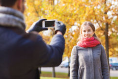 Smiling couple with smartphone in autumn park Royalty Free Stock Photography