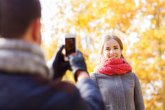 Smiling couple with smartphone in autumn park Stock Photo