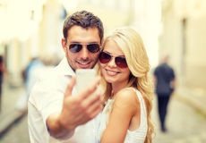 Smiling couple with smartphone in the city Royalty Free Stock Photos