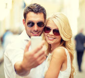 Smiling couple with smartphone in the city Stock Photography