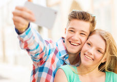 Smiling couple with smartphone in city Stock Photos
