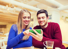 Smiling couple with smartphone drinking tea Stock Photo