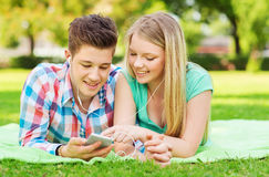 Smiling couple with smartphone and earphones Stock Photography