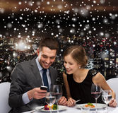 Smiling couple with smartphone at restaurant Stock Images
