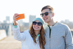 Smiling couple with smartphone taking selfie Stock Images