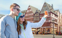 Smiling couple with smartphone taking selfie Royalty Free Stock Images