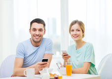 Smiling couple with smartphones reading news Royalty Free Stock Image