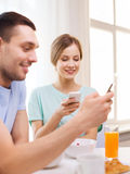 Smiling couple with smartphones reading news Royalty Free Stock Photo