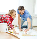 Smiling couple smearing wallpaper with glue Royalty Free Stock Image
