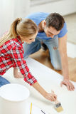 Smiling couple smearing wallpaper with glue Royalty Free Stock Photos