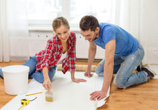 Smiling couple smearing wallpaper with glue Stock Photos