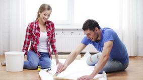 Smiling couple smearing wallpaper with glue stock footage