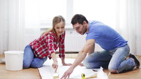 Smiling couple smearing wallpaper with glue stock video footage