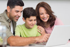 Smiling couple with son using laptop Stock Image