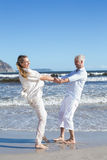 Smiling couple spinning on the beach Royalty Free Stock Photos