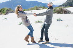 Smiling couple spinning on the beach in warm clothing Royalty Free Stock Photos