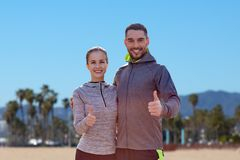 Smiling couple in sport clothes showing thumbs up Stock Image