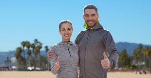 Smiling couple in sport clothes showing thumbs up. Fitness, sport and gesture concept - smiling couple outdoors showing thumbs up over venice beach background in stock photography