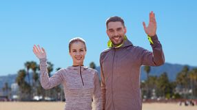 Smiling couple in sport clothes waving hand Royalty Free Stock Photos