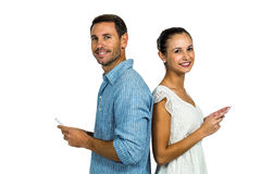 Smiling couple standing back to back using smartphones Stock Photo