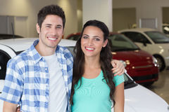 Smiling couple standing in front of a car Royalty Free Stock Photos