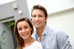 Smiling couple standing in front of house Royalty Free Stock Photos