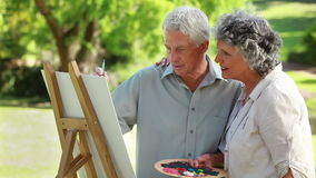 Smiling couple standing in front of a wooden easel Royalty Free Stock Photography