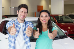 Smiling couple standing while giving thumbs up Royalty Free Stock Image