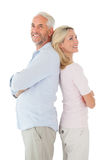 Smiling couple standing leaning backs together Stock Photo