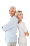 Smiling couple standing leaning backs together Royalty Free Stock Images
