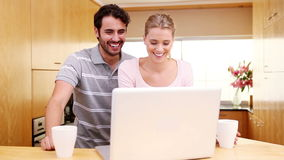Smiling couple standing while looking at a laptop stock video footage