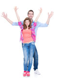 Smiling couple standing with raised hands. Stock Photos