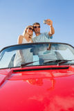 Smiling couple standing in red cabriolet taking picture Stock Photos