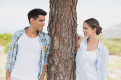 Smiling couple standing by tree trunk Royalty Free Stock Photography