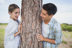 Smiling couple standing by tree trunk Stock Image