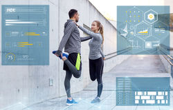 Smiling couple stretching leg outdoors. Fitness, sport and people concept - smiling couple stretching leg outdoors Stock Image