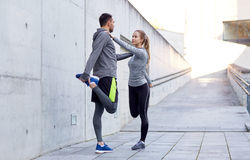 Smiling couple stretching leg outdoors. Fitness, sport, people and lifestyle concept - smiling couple stretching leg outdoors Stock Images