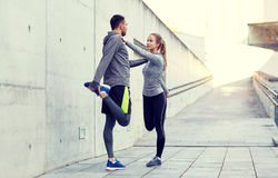 Smiling couple stretching leg outdoors. Fitness, sport, people and lifestyle concept - smiling couple stretching leg outdoors Royalty Free Stock Photography