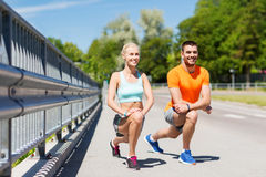 Smiling couple stretching leg outdoors. Fitness, sport, training and lifestyle concept - smiling couple stretching leg outdoors Royalty Free Stock Photography