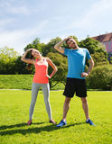 Smiling couple stretching outdoors. Fitness, sport, training and lifestyle concept - smiling couple stretching outdoors Stock Photos
