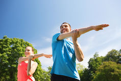 Smiling couple stretching outdoors. Fitness, sport, training and lifestyle concept - smiling couple stretching outdoors Stock Image
