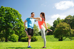 Smiling couple stretching outdoors. Fitness, sport, training and lifestyle concept - smiling couple stretching outdoors Stock Photography