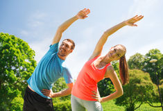 Smiling couple stretching outdoors. Fitness, sport, training and lifestyle concept - smiling couple stretching outdoors Royalty Free Stock Photos