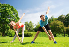 Smiling couple stretching outdoors. Fitness, sport, training and lifestyle concept - smiling couple stretching outdoors Royalty Free Stock Photography