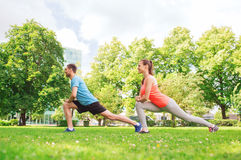 Smiling couple stretching outdoors. Fitness, sport, training and lifestyle concept - smiling couple stretching outdoors Royalty Free Stock Image