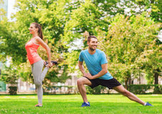 Smiling couple stretching outdoors. Fitness, sport, training and lifestyle concept - smiling couple stretching outdoors Royalty Free Stock Images