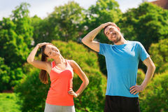Smiling couple stretching outdoors. Fitness, sport, training and lifestyle concept - smiling couple stretching outdoors Stock Images