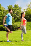 Smiling couple stretching outdoors. Fitness, sport, training and lifestyle concept - smiling couple stretching outdoors Royalty Free Stock Photo