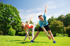 Smiling couple stretching outdoors Stock Images
