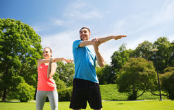 Smiling couple stretching outdoors. Fitness, sport, training and lifestyle concept - smiling couple stretching outdoors Stock Photo